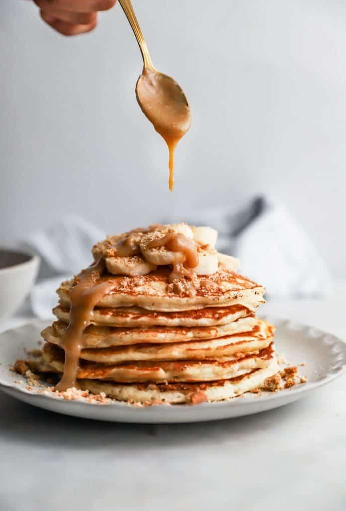 spoon dripping toffee sauce onto banoffee pancakes