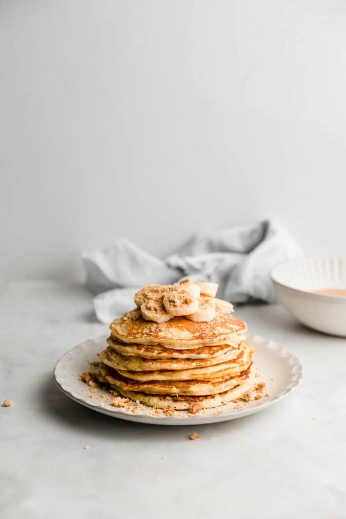 stack of pancakes with banana and a bowl of toffee in background