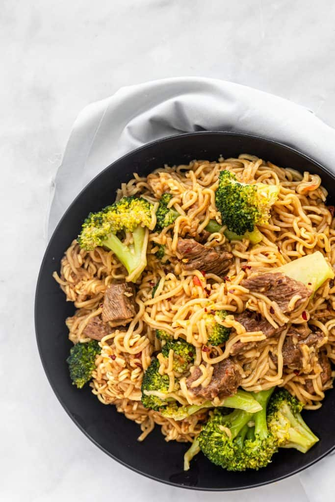 complete bowl of instant pot beef and broccoli noodles with a kitchen linen in the background