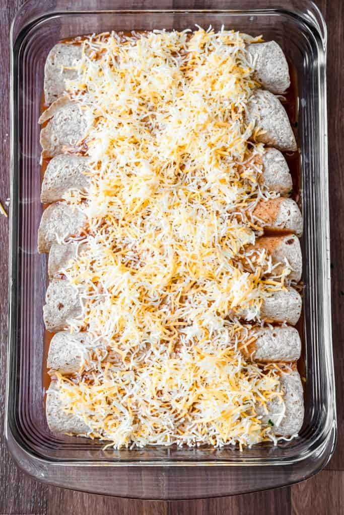 unbaked pan of enchiladas with cheese on top