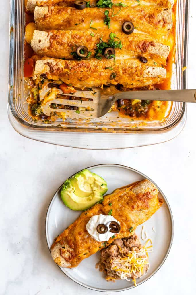 an assembled plate of veggie enchiladas with sliced avocado and refried beans