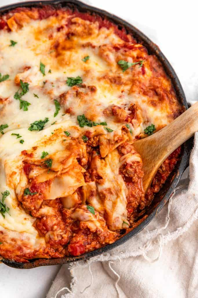 wooden spoon taking a scoop of lasagna out of skillet