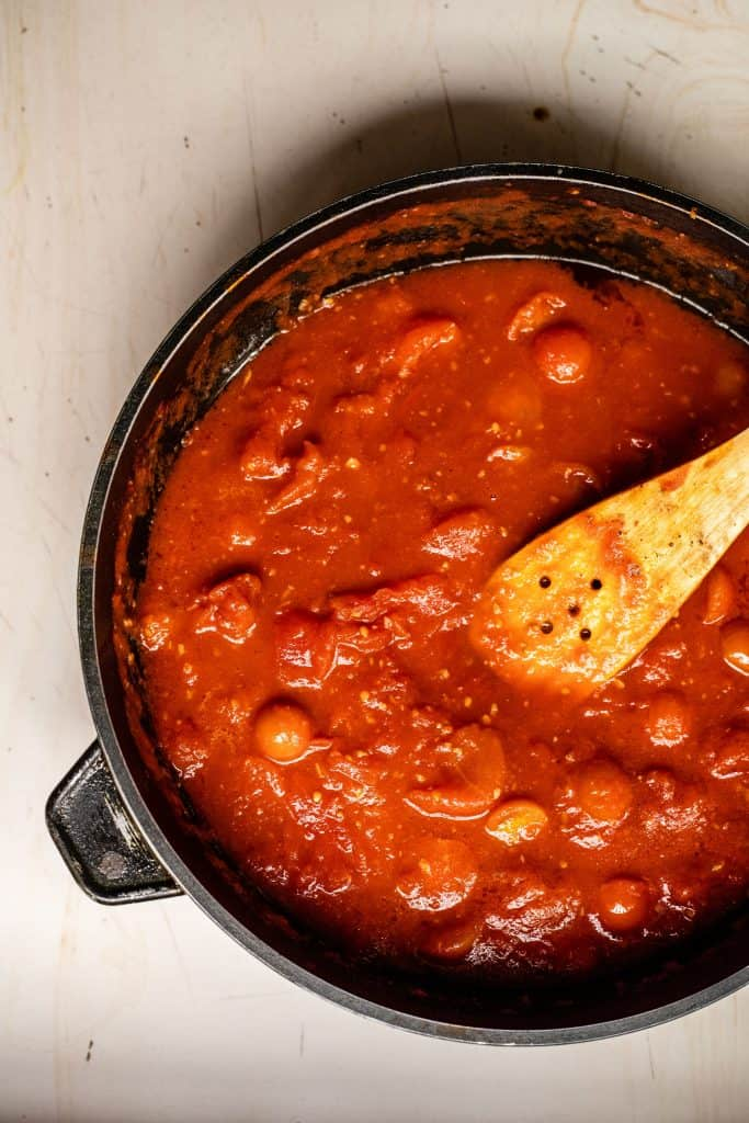 cherry tomato pasta sauce in a skillet with a wooden spoon