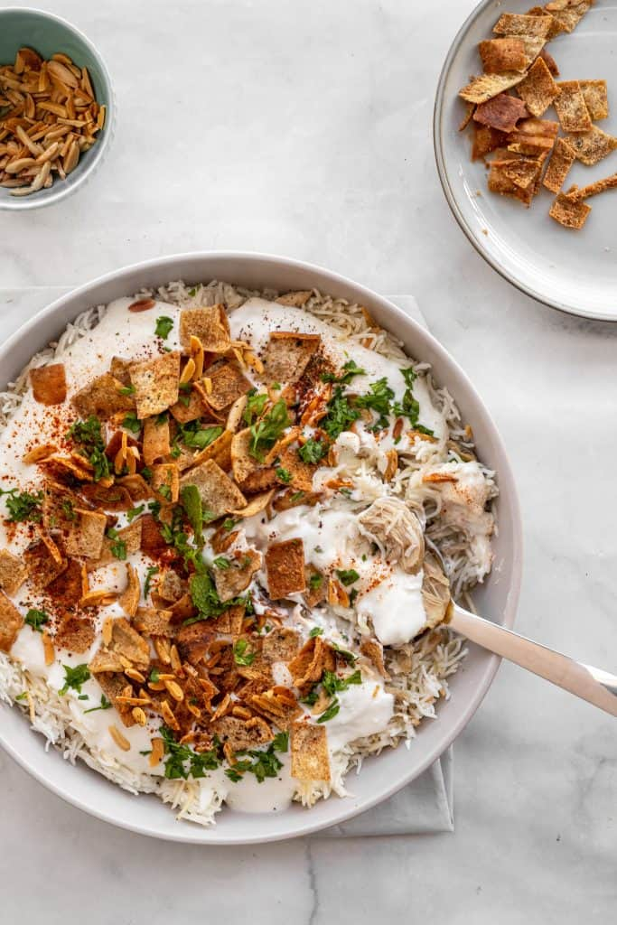 assembled chicken fatteh with toasted pita bread and nuts in bowls in the corner