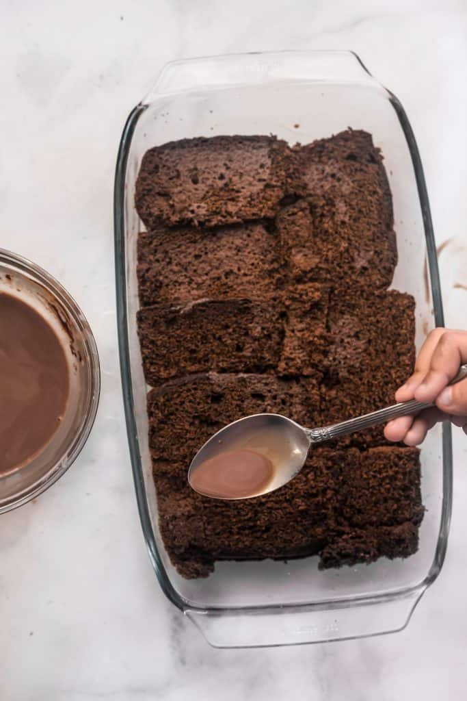 pouring chocolate milk on chocolate cake in pyrex