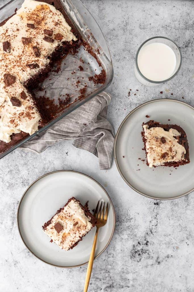 pan of  chocolate poke cake with some slices on plates and a glass of milk