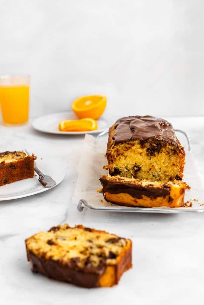 chocolate orange cake sliced and cut up with a glass of orange juice on the background with oranges on a plate
