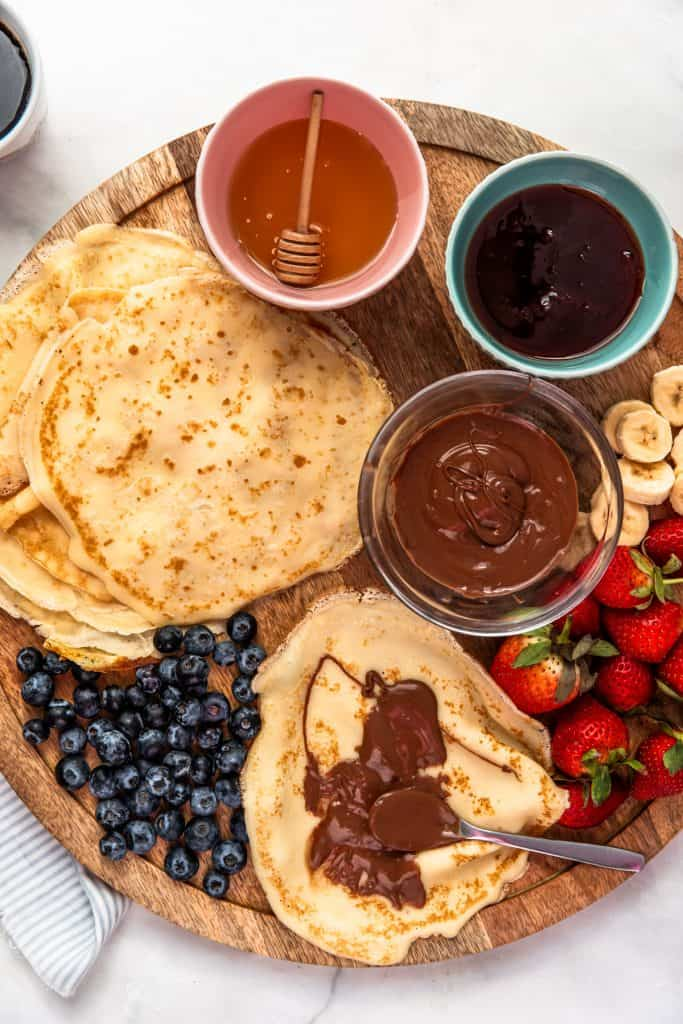 circular board with crepes and toppings on it with nutella on crepe