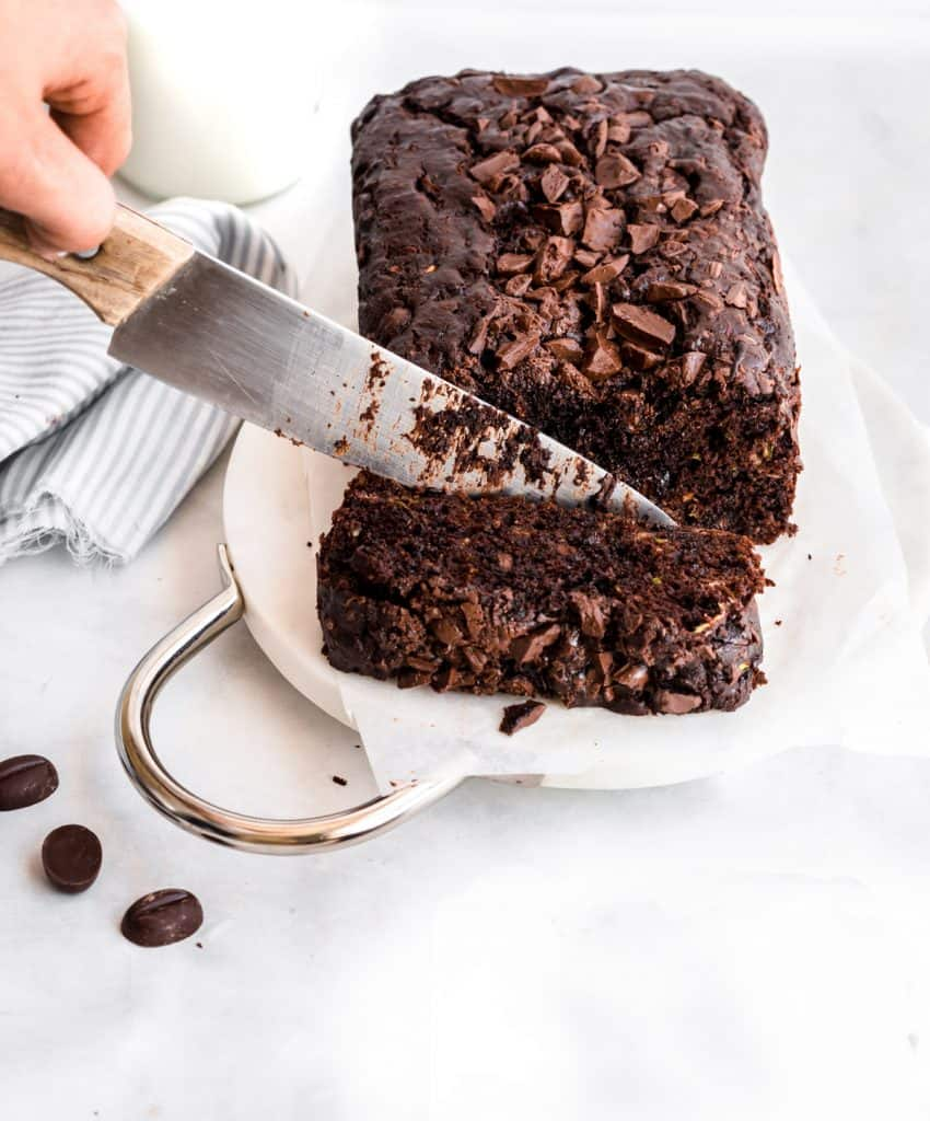 knife cutting into a loaf of moist chocolate zucchini bread