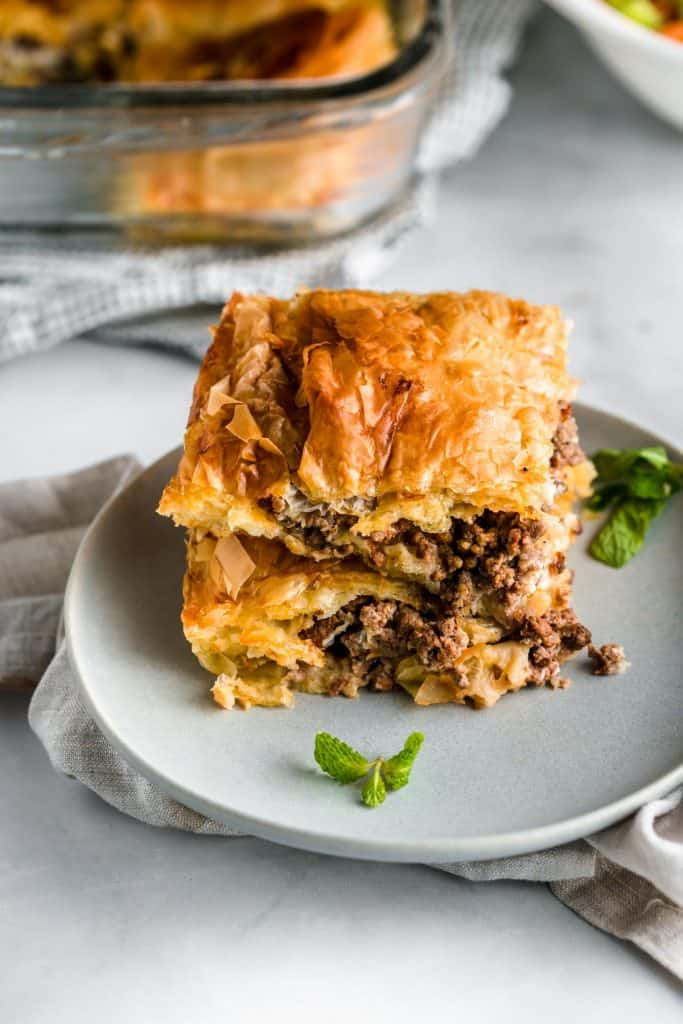 two slices of phyllo meat pie stacked on top of a plate