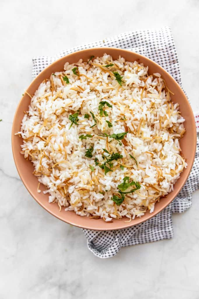 top shot of vermicelli Egyptian rice in a tan bowl with a kitchen towel