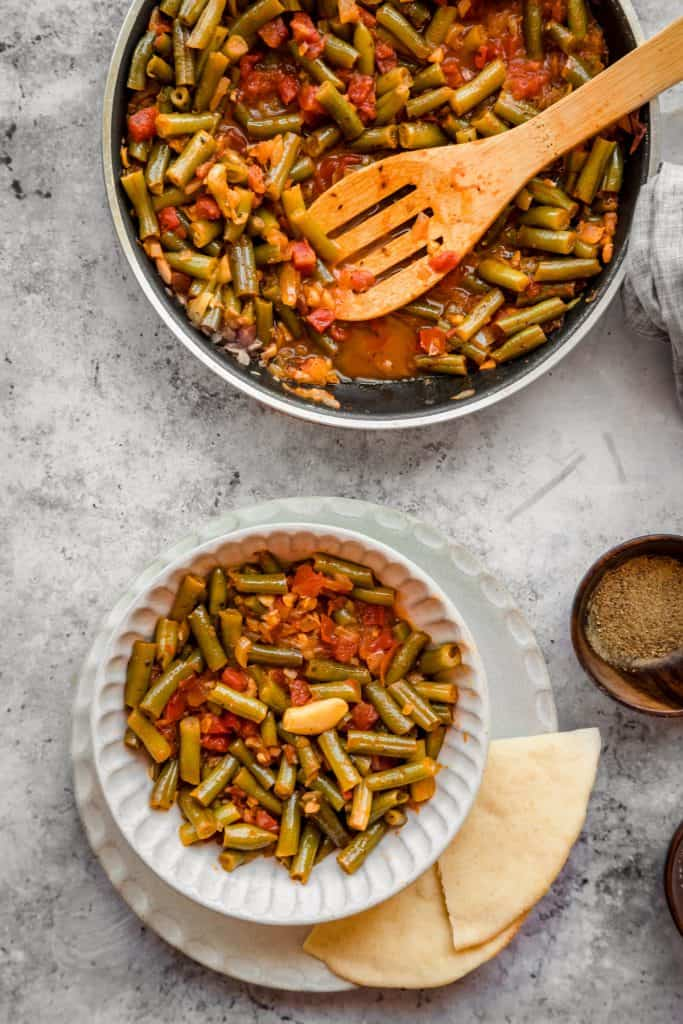 Bowl of lebanese green beans with pita bread and spices on the side