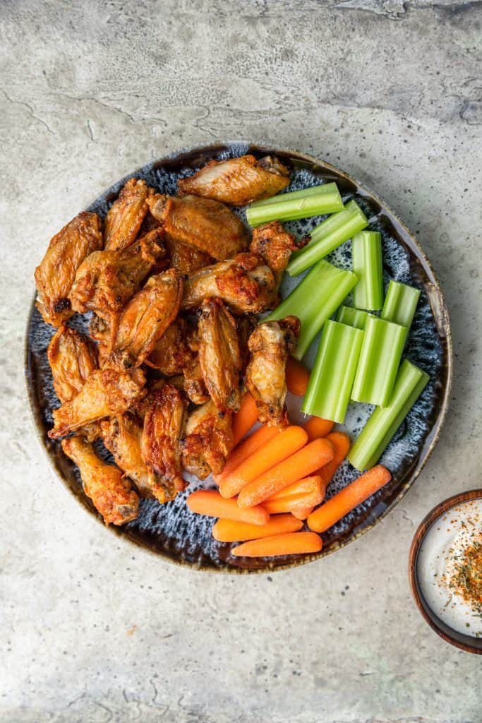 plate of air fryer chicken wings with carrot and celery sticks