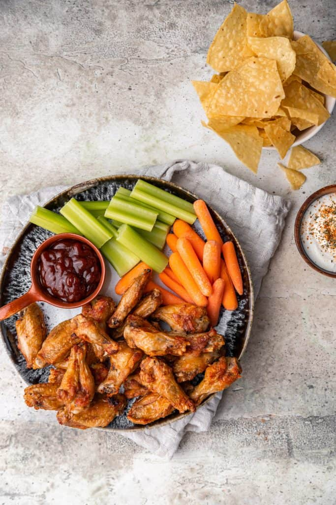 air fryer chicken wings in a plate with carrots and celery with dipping sauces on the side