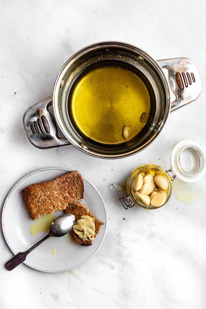 Flatlay photo of garlic confit on bread and a jar of garlic confit