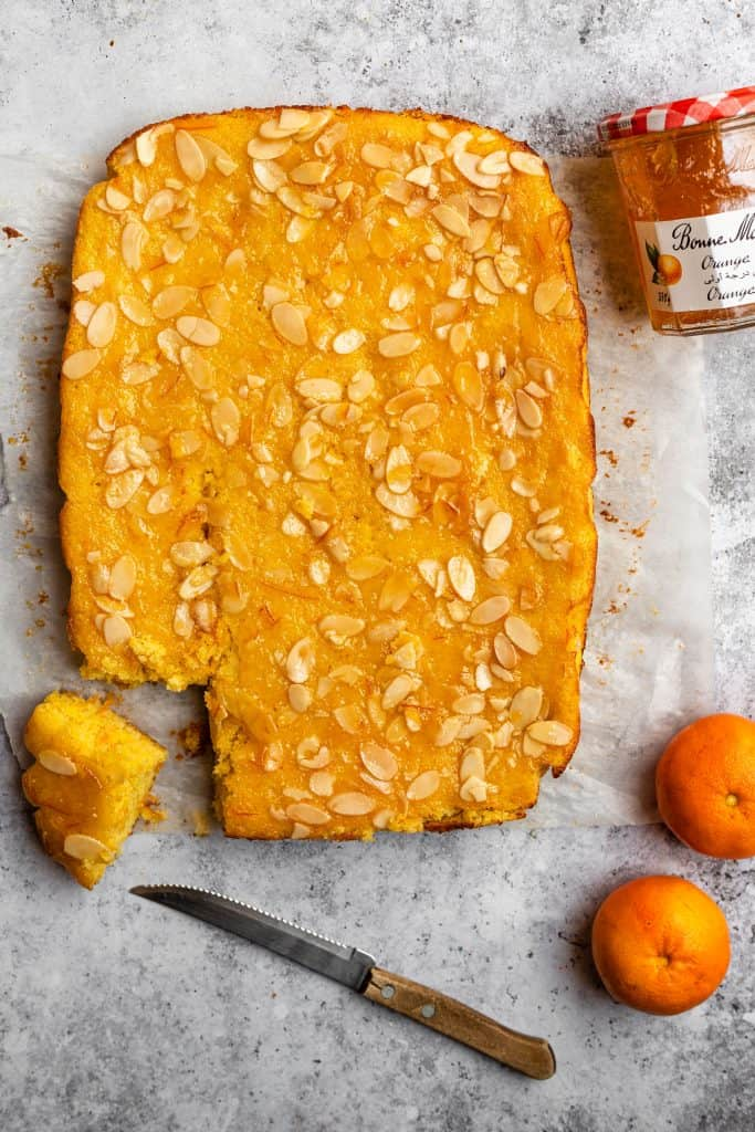 whole gluten free orange almond cake with some oranges on the side and marmalade