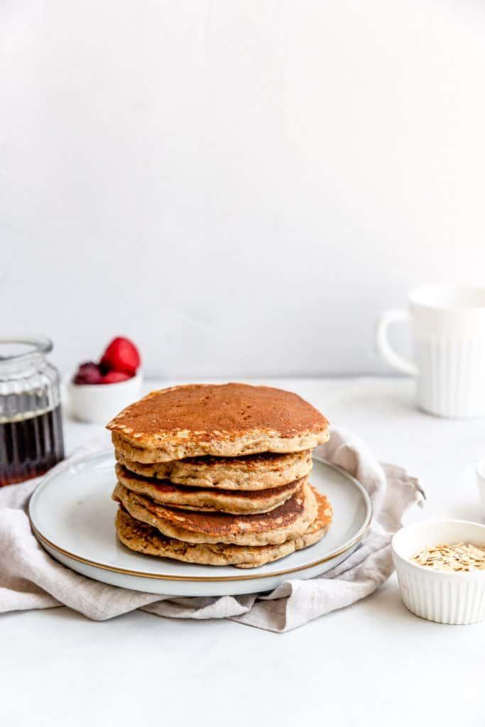 stack of pancakes on plate with coffee mug