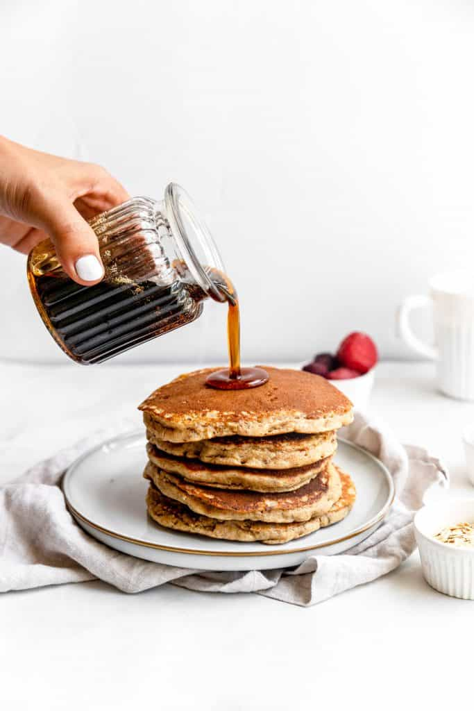 hand holding a glass full of maple syrup pouring onto harvest grain pancakes