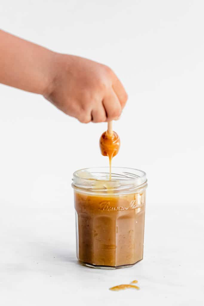 hand holding a honey stick dripping with caramel out of a jar
