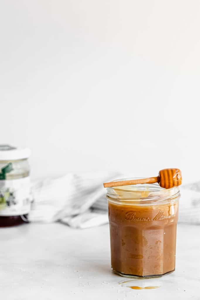 Honey caramel sauce in a jar with honey in the background