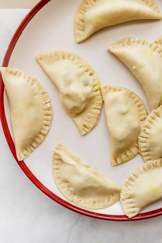assembled raw empanadas on a plate before flying