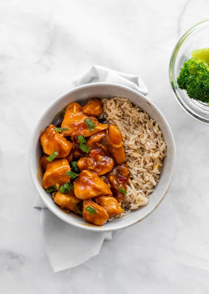 Orange chicken in a bowl with brown rice with broccoli on the side