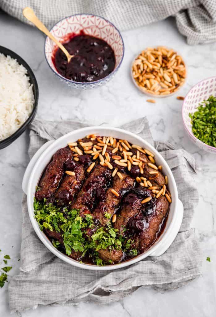 kabab bil karaz with plates of garnish around it