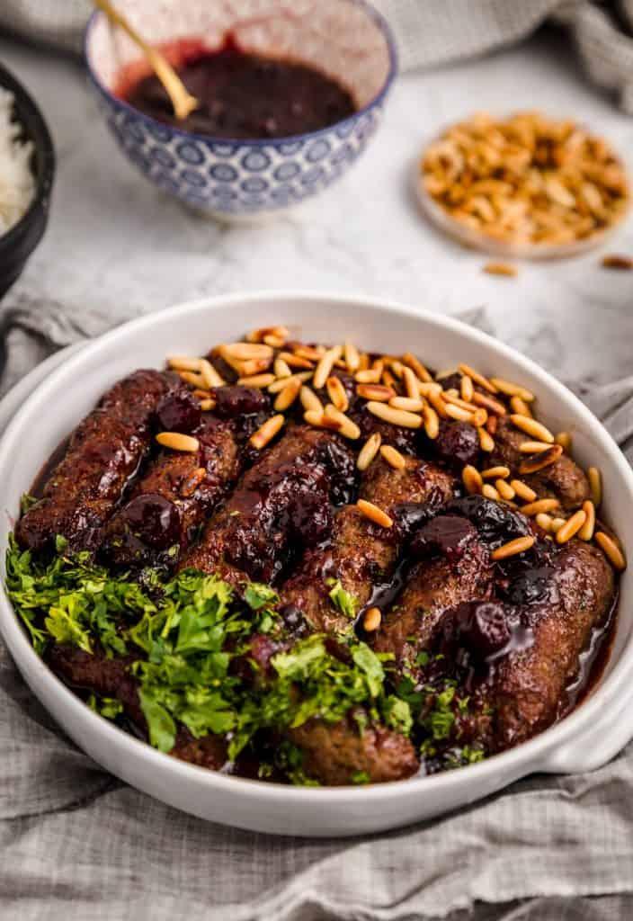close up photo of garnished kebab bilkaraz with small bowls of garnish around it