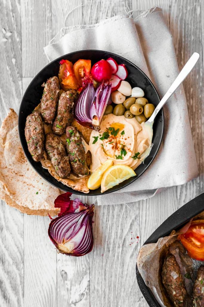 a plate of cooked kafta with hummus and veggies and olives with pita bread on the side