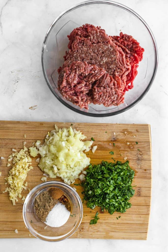 ground meat in a bowl with chopped onions and parsley on chopping board