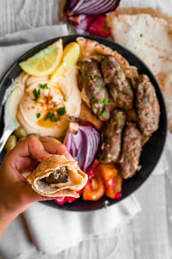 kafta sandiwch held over a plate of cooked kafta with hummus and veggies and olives with pita bread on the side
