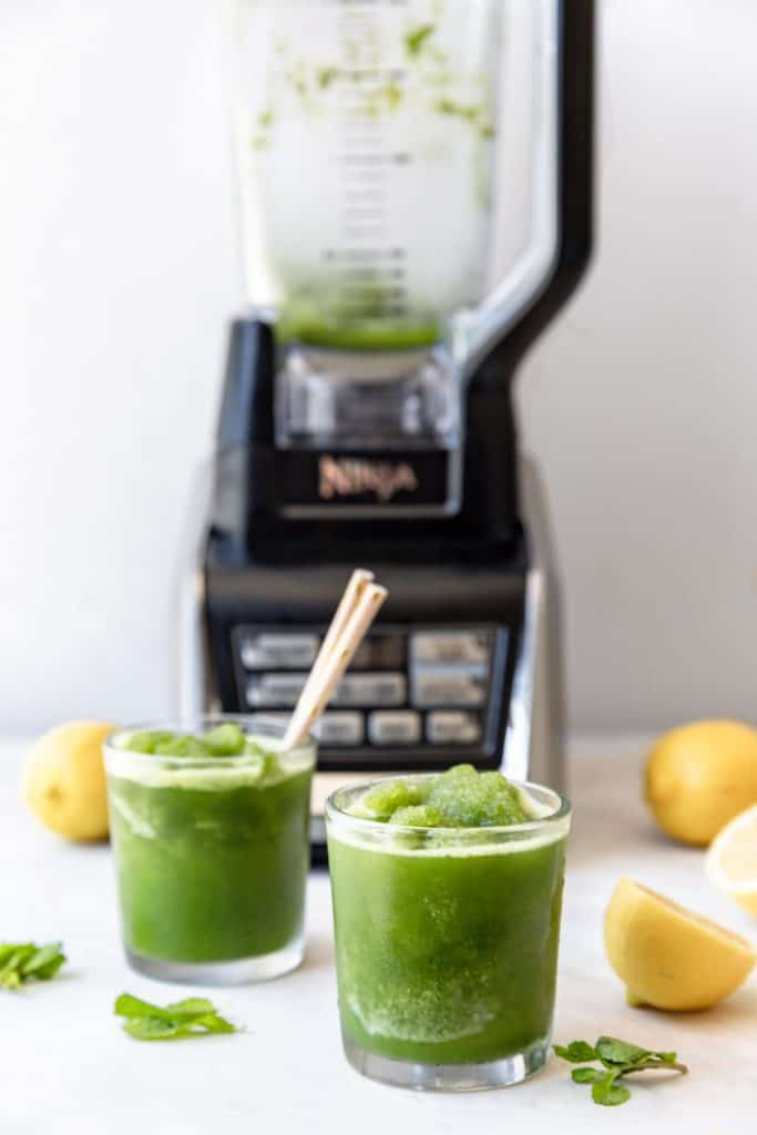 two cups of mint lemonade in front of a ninja blender
