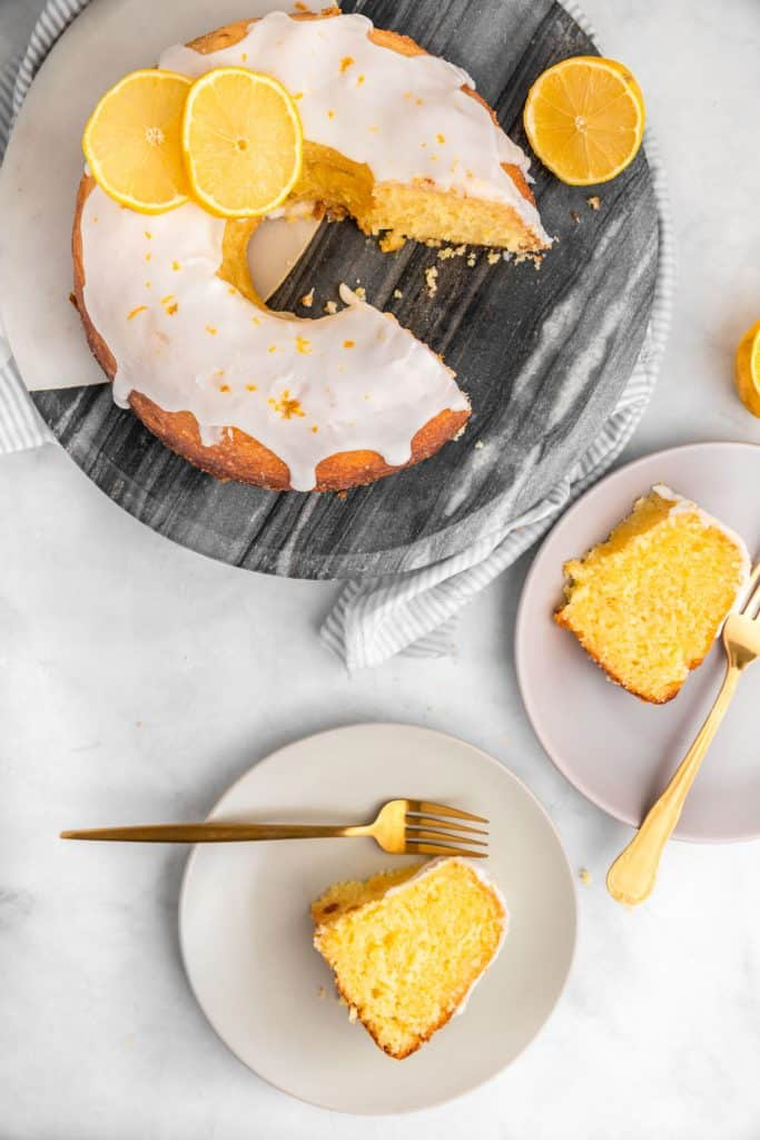 two plates with slices of lemon bliss cake and rest of cake in background