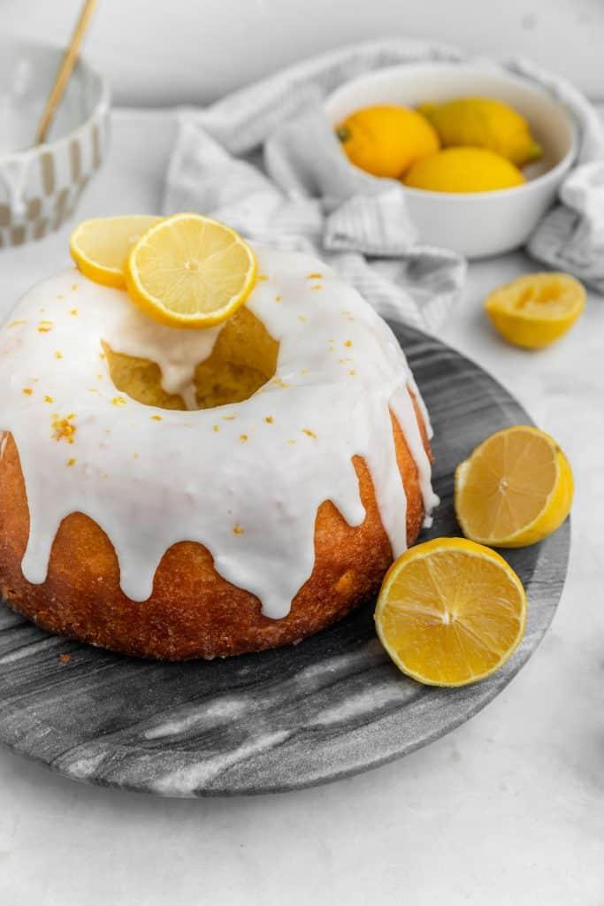 lemon bundt cake with bowl of lemons in the background