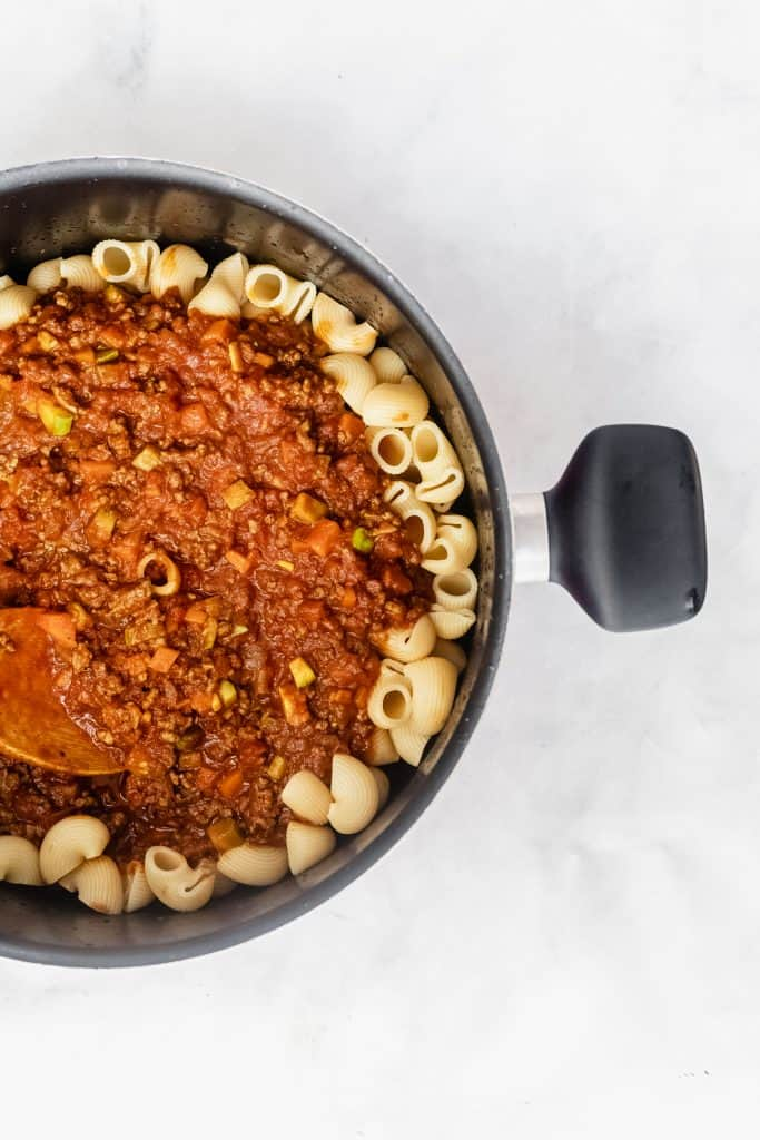elbow macaroni in a pot with beef tomato sauce on top before mixing