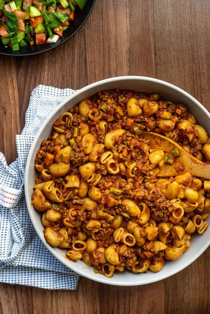 cooked middle eastern style macaroni in a white bowl with a kitchen towel