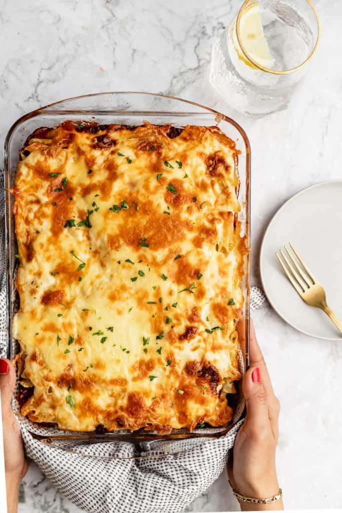 hands holding a pan of macarona bechamel