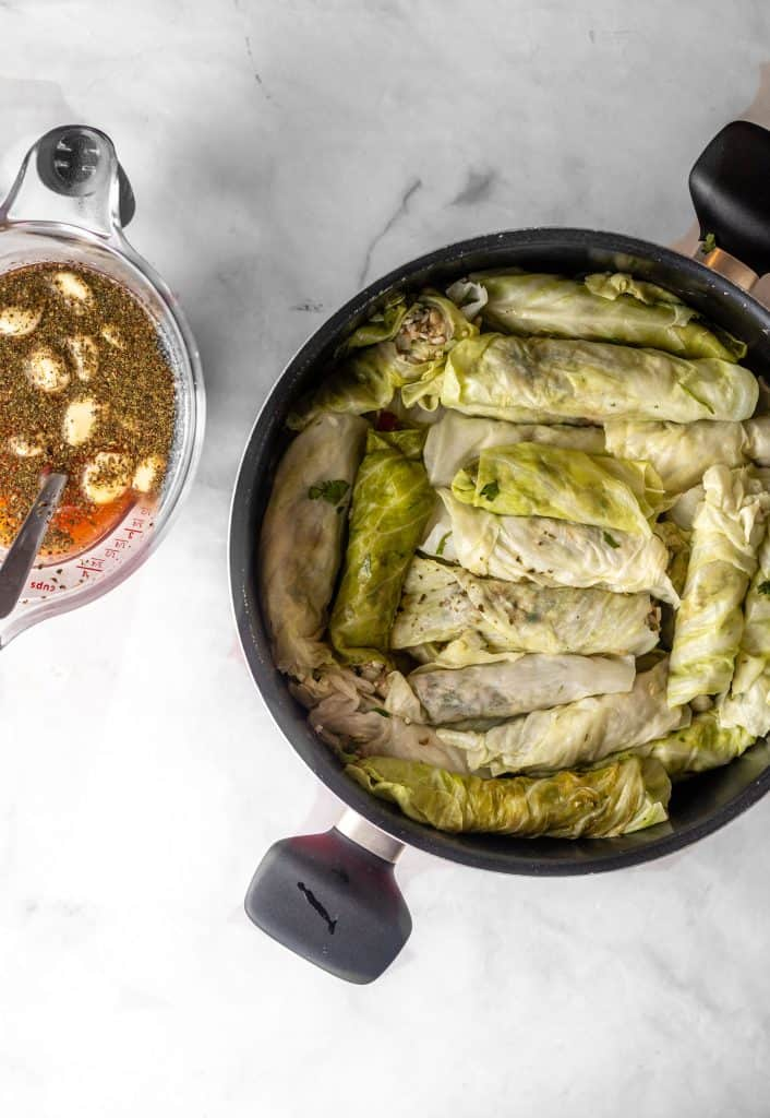 assembled cabbage rolls in pot with broth in a measuring cup on the side