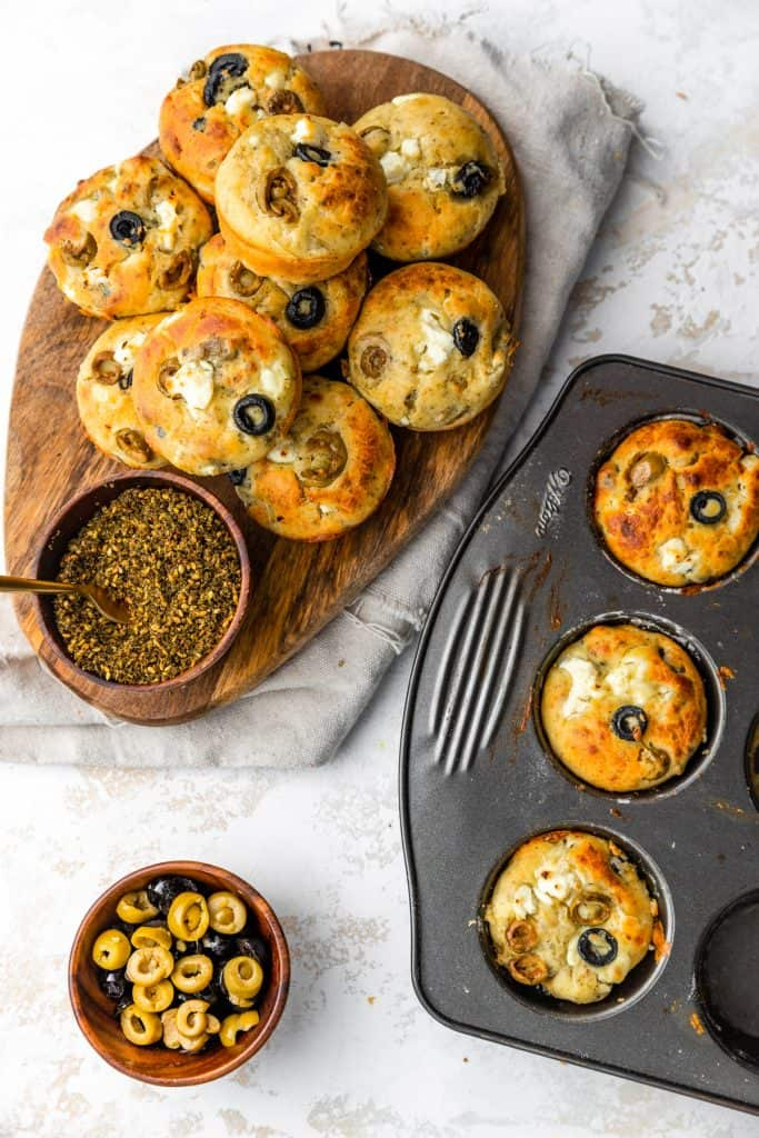 pile of mediterranean muffins on a wooden board with some baked muffins in a tray