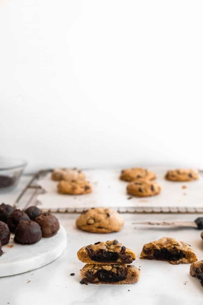 truffles stuffed chocolate chip cookies cut in the middle with more on a baking sheet in the background