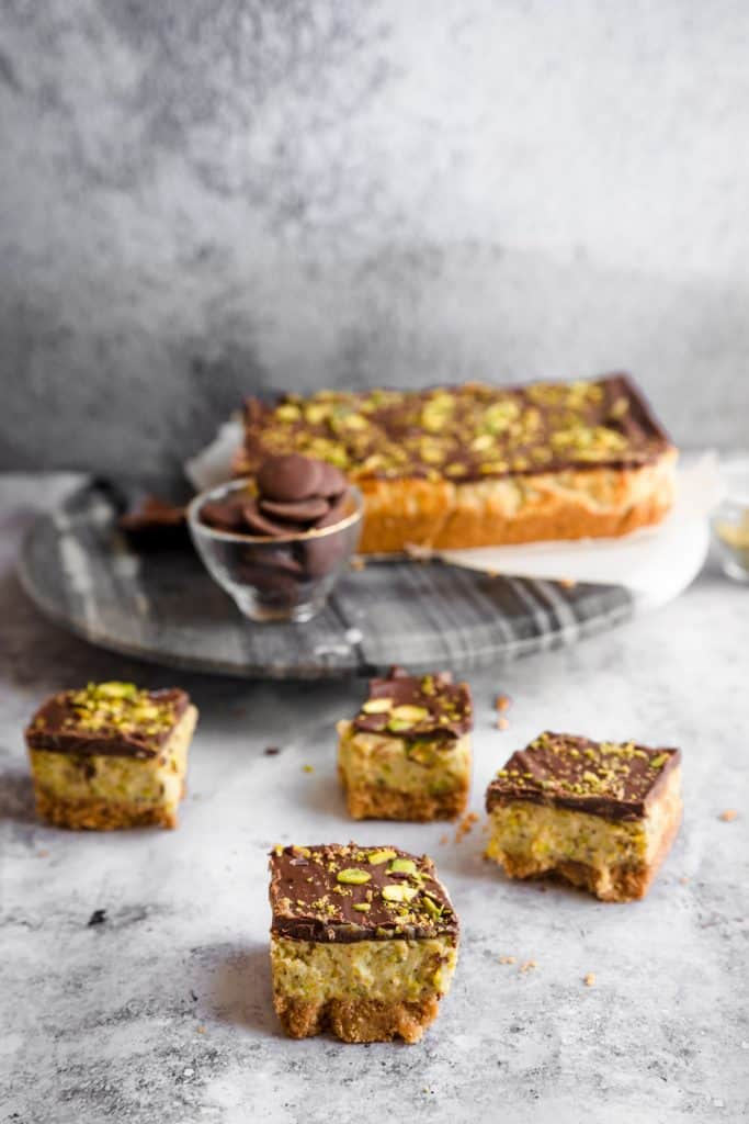 pistachio cheesecake bars with chocolate in the background