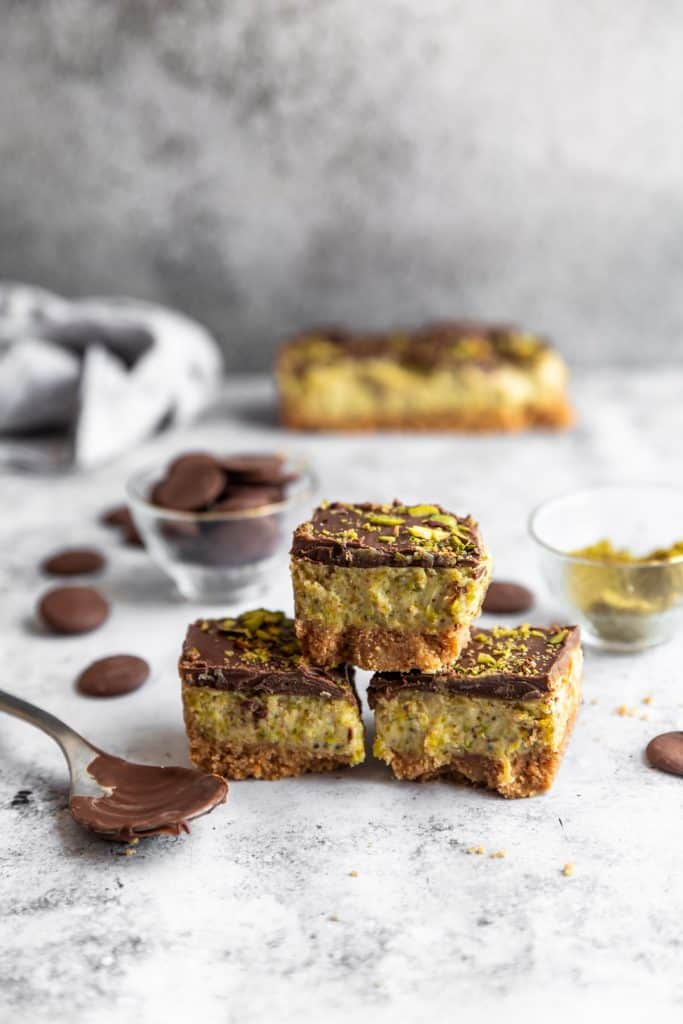 pistachio cheesecake stacked on top of each other with a spoon of chocolate