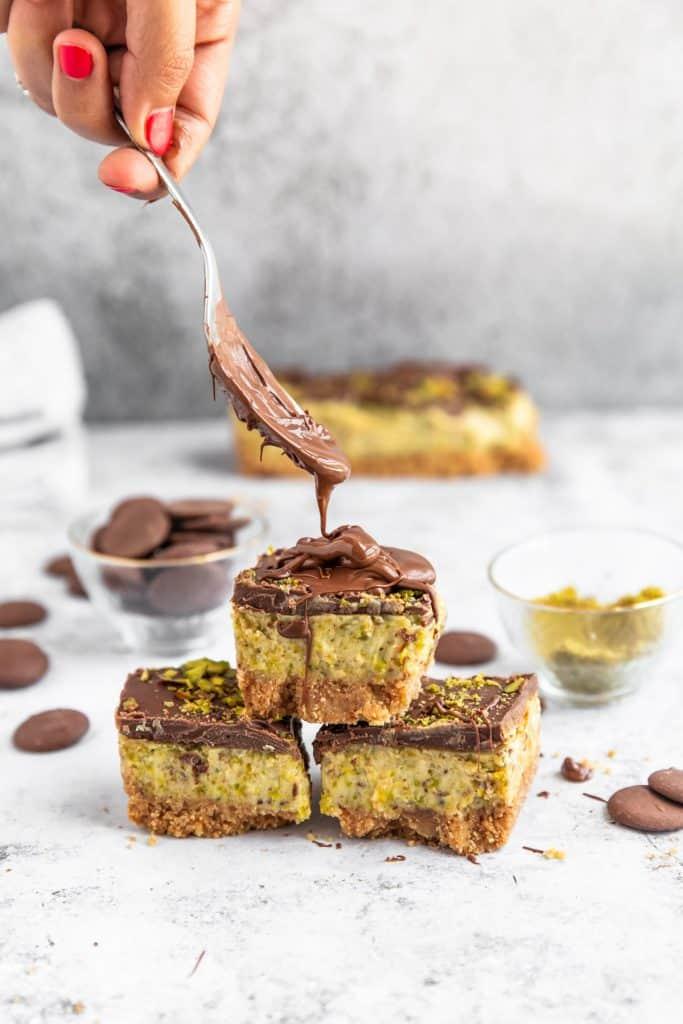 spoon dripping chocolate onto pistachio cheesecake bars