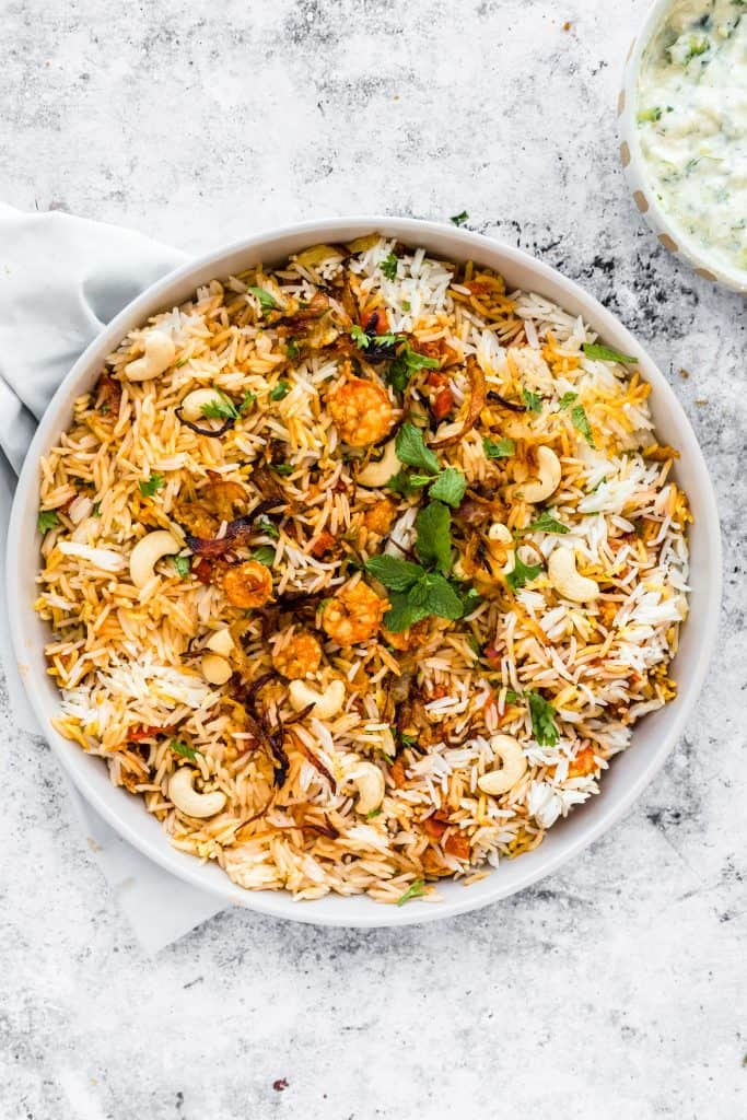 bowl of prawn biryani with raita in a bowl in the corner