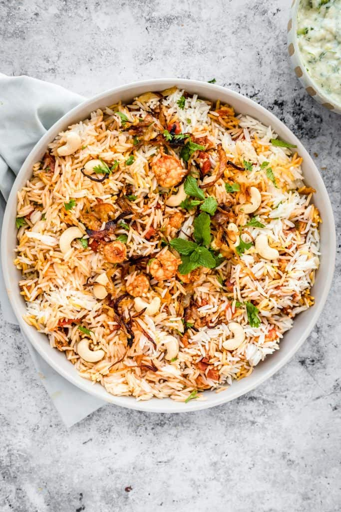 bowl of biryani with raita in a bowl in the corner