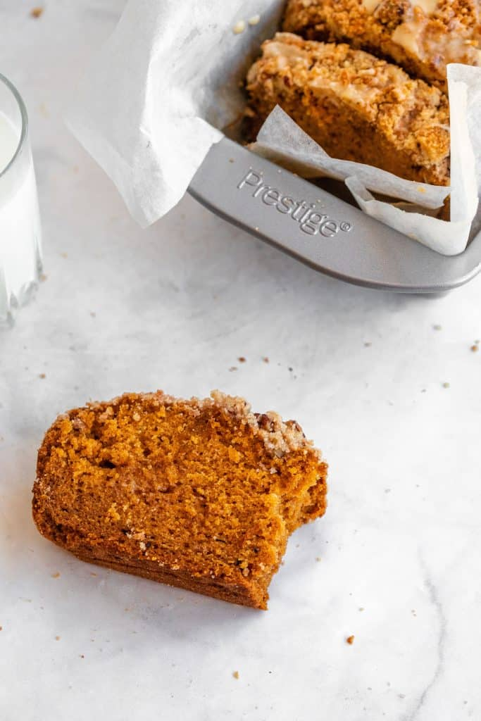 slices of pumpkin bread in loaf pan with one slice of bread with a bite taken out