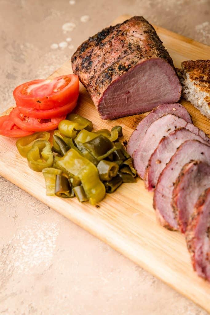 close up photo of the sliced tenderloin on wooden platter