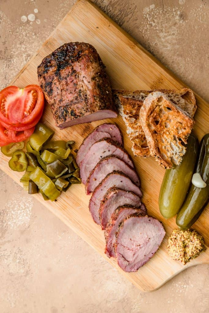 Sliced smoked beef tenderloin on a wooden platter with pickles and tomatoes