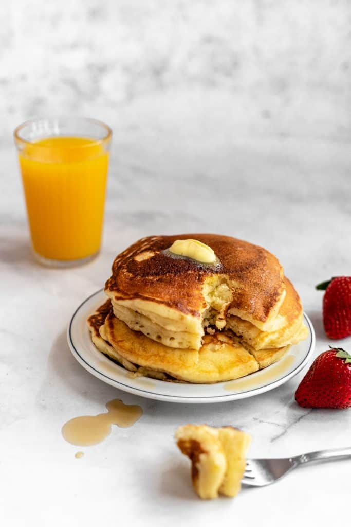 Stack of fluffy and delicious sour milk pancakes with strawberries on the side and bite taken out