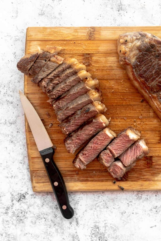 Sliced sous vide rib eye steak on chopping board